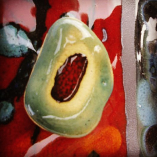 #Enamelled_ceramic #sea_wore_pebble on a #red_background with green marks coming from #melted_glass.